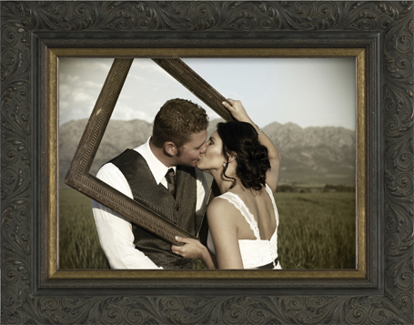 Custom frame design with young couple kissing through an empty frame with mountains and fields in the background.