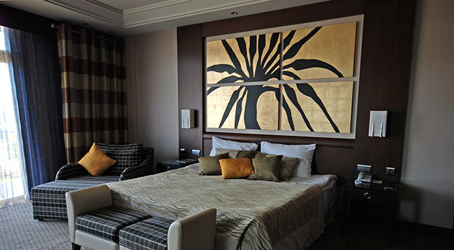 Photo of beautifully decorated hotel bedroom with four piece custom framed artwork on the wall.