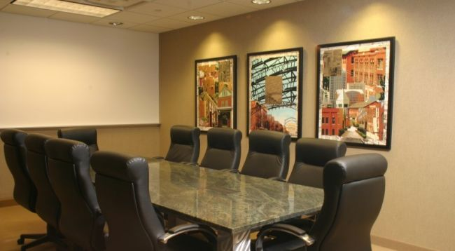 Conference room with conference table, chairs and beautifully framed custom artwork.