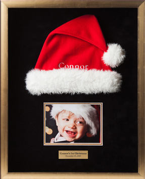 Shadowbox with Santa had and picture of child wearing hat commemorating childs first Christmas.