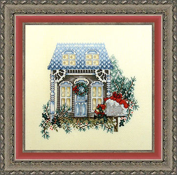Framed piece showing a cross stitched piece of art depicting a home and landscaping.