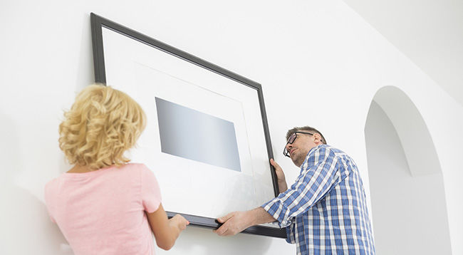 Man and woman hanging a framed piece on a wall