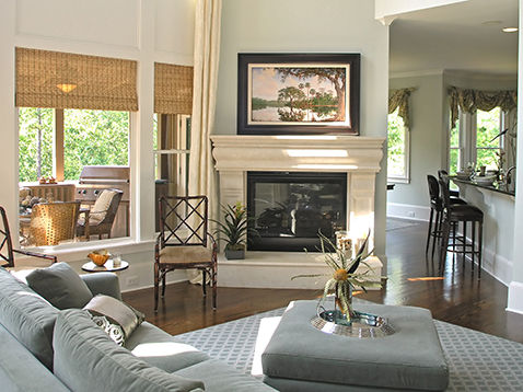 Photograph of nicely decorated living space with a large custom framed landscape over the fireplace.