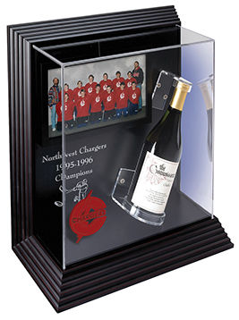 Acrylic case displaying a team picture and a bottle of champagne