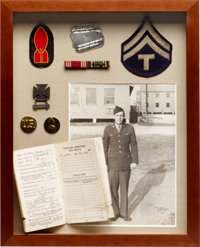 Shadowbox frame with various pieces of military memorabilia.