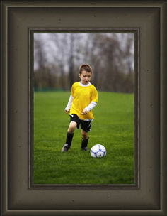 Custom framed picture of young soccer player about to kick a soccer ball.