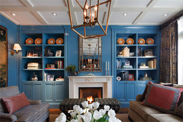 Living room with built in bookcases surrounding fireplace and beautiful custom framed mirror.