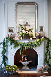 Fireplace with custom framed mirror above beautifully decorated for holiday season.