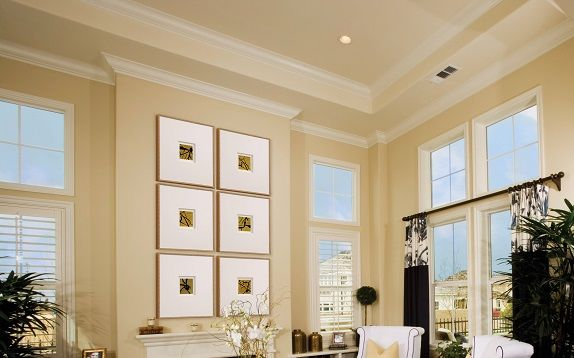 Traditional room setting with multiple framed pieces over a fireplace.