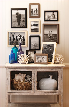 Decorative table decorated with seaside accents that has multiple photos framed in ready made frames hanging above it.