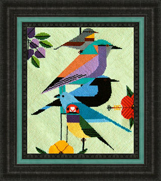 Framed needle art showing abstract birds nesting with flowers.